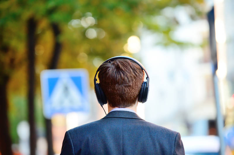 Man in suit listening to a podcast through his headphones