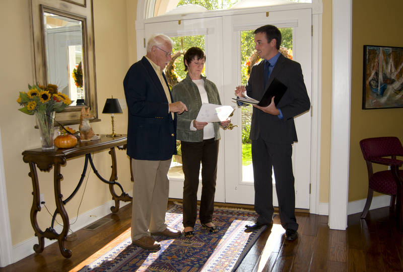 An open for inspection with a real estate agent and an older couple.